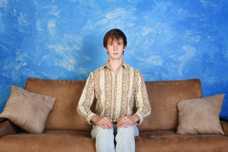 upright: Young Caucasian man sits straight on sofa