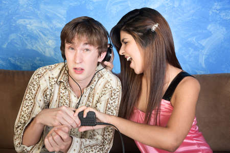 Beautiful young woman distracts man listening to music Stock Photo - 10833423