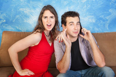 couple on couch: Angry woman listens to man on phone call  Stock Photo