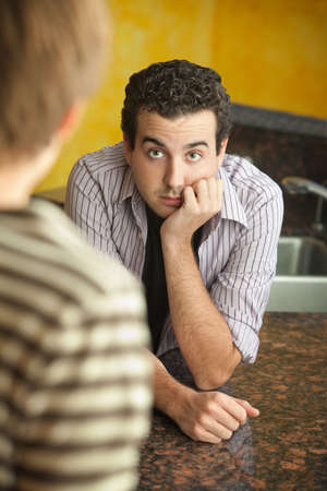 Worried young Caucaisian man with hand on chin in kitchen photo