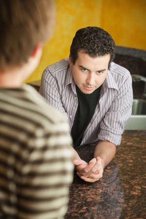 insecure: Unsure young man with friend in kitchen  Stock Photo