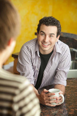 chit chat: Young handsome man with friend enjoys mug of coffee or tea in kitchen