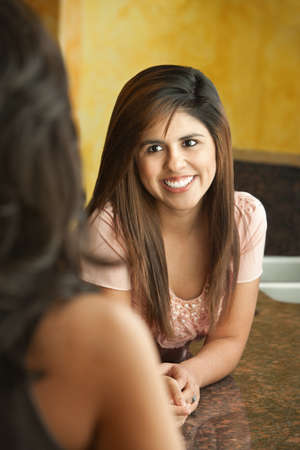 Young Hispanic woman learning on counter smiles at friend  Stock Photo - 10833410