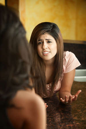 Worried young girl talks with friend at a granite table