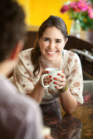 Smiling young Caucasian woman enjoys mug of coffee or tea photo