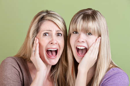 Mother and daughter scream with hands on their faces photo
