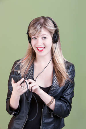 Retro-styled young Caucasian woman listens to music on headphones over green background Stock Photo - 10833420