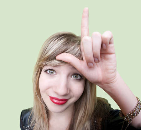 brat: Cute young Caucasian woman makes loser sign on her forehead over green background