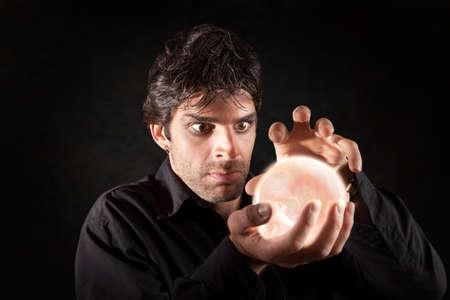 fortuneteller: Male fortune-teller gazes over a crystal ball Stock Photo