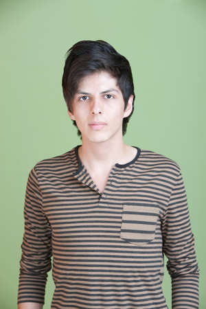 Serious young Hispanic man over green background