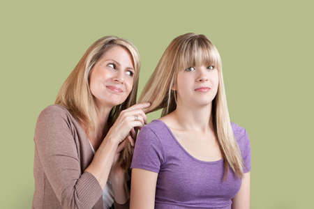 Smiling Caucasian mom with annoyed daughter over green background