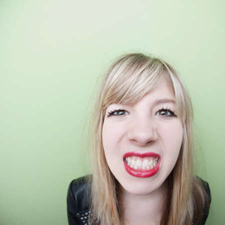 Young Caucasian lady clenches her teeth over green background photo