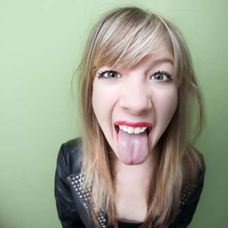 brat: Cute young woman sticks out her tongue over green background