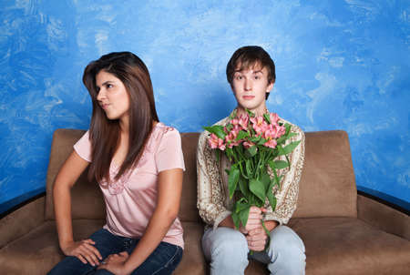 spat: Innocent young man holds flower bouquet while his girlfriend looks away