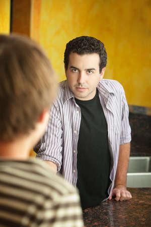 angry teenager: Serious young Caucasian man with friend in kitchen Stock Photo