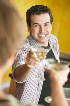 chit chat: Young Caucasian man with friend makes a toast with martini glass Stock Photo