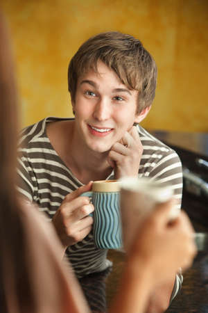 chit chat: Young Caucasian man with friend enjoys mug of coffee or tea