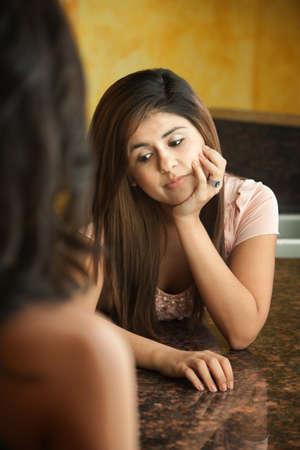 daydream: Worried young Hispanic teen with hand on chin
