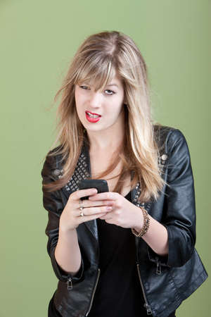 wind blown hair: Retro-styled young Caucasian lady types text message on her cellphone over green background