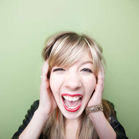 mouth close up: Young Caucasian woman screams with ears covered