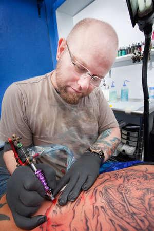 Caucasian tattoo artist uses machine to ink a tattoo  photo