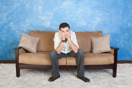face centered: Bored young Caucasian man rests on sofa with hands on face  Stock Photo