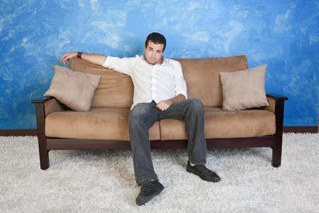 Lazy jonge blanke man zit in het midden van bank