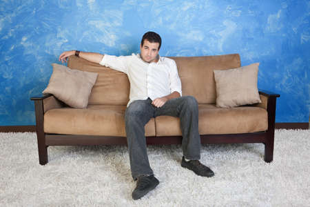 face centered: Lazy young Caucasian man sits in middle of couch