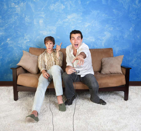 video game: Excited young man plays video games with friend Stock Photo