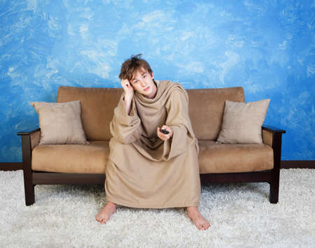 face centered: Bored teen in brown bathrobe with remote control in hand