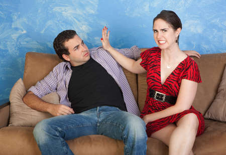 Furious woman gestures to slap man on sofa photo