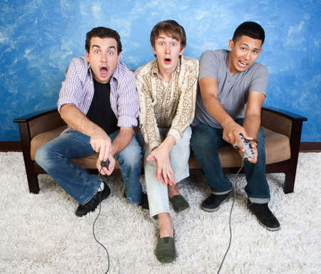 Three excited friends with controllers play video games