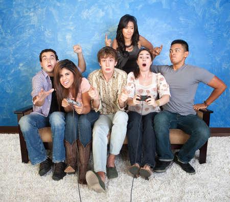 suspens: Groupe de six amis avec les contr�leurs excit�s jouer � des jeux vid�o