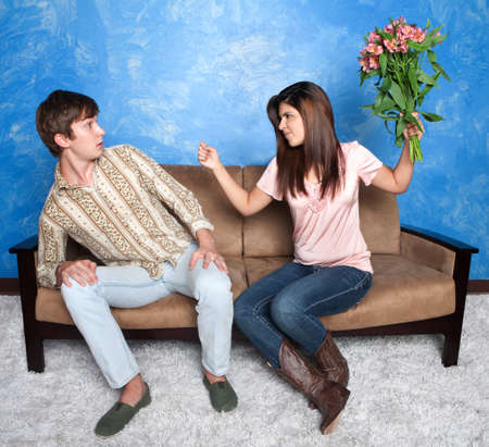 Unhappy Hispanic girl gestures to throw bouquet on boyfriend photo
