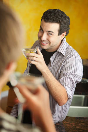 tipsy: Happy young Caucasian man enjoys martini with his friend in kitchen