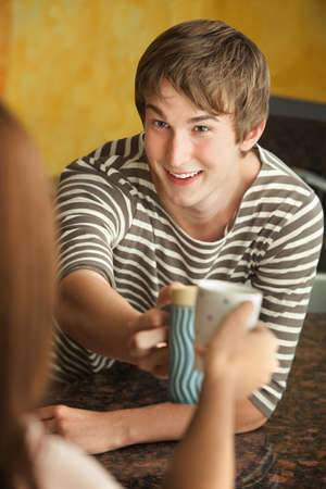 Young Caucasian guy with friend toast with coffee mugs photo