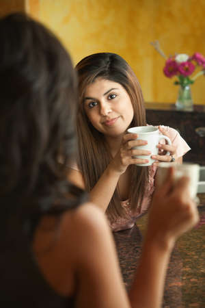 Young Hispanic women with coffee chat in kitchen Archivio Fotografico