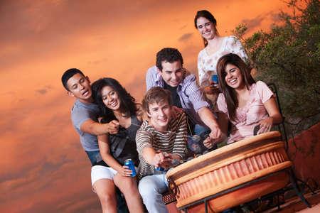 latino family: Group of six happy friends toast marshmallows