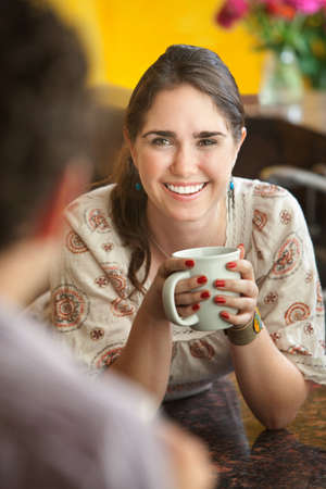 Happy young Caucasian lady with mug and friend photo