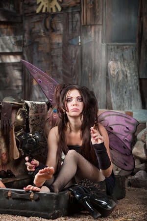 Beautiful fairy sitting in suitcase holds black roses and smokes cigar photo