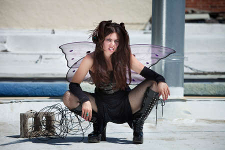 Attractive fairy sitting outdoors on a silver roof photo