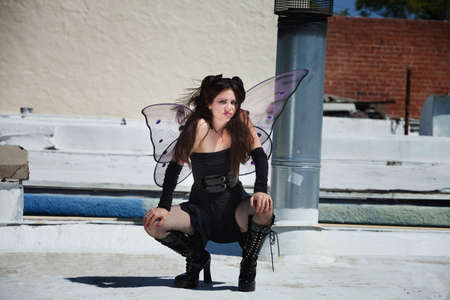 Annoyed fairy squats outdoors in black outfit