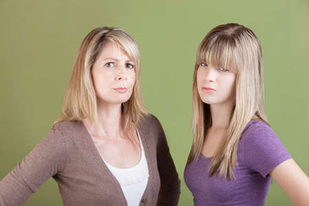 Caucasian mom and daughter over green background frown