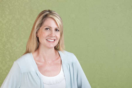 sexy mature women: Mature Caucasian woman smiles over green background