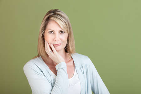 Mature Caucasian woman with hand on chin over green background Stock Photo