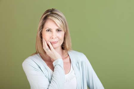 donne mature sexy: Maturo donna caucasica con la mano sul mento su sfondo verde