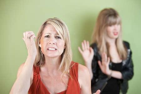 desconfianza: Desdichada madre con la hija de frustraci�n sobre fondo verde Foto de archivo