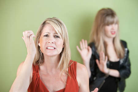 suspicious: Unhappy mother with frustrated daughter over green background Stock Photo