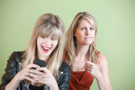 Upset woman with laughing teen on cell phone photo