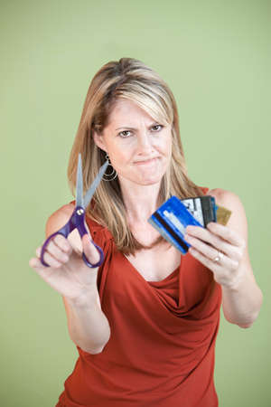 Upset mature woman ready to cut credit cards using scissors photo